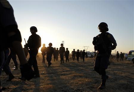 Special task force members and policemen walk back to their cars after protesting miners were shot outside a South African mine in Rustenburg, 100 km (62 miles) northwest of Johannesburg, August 16, 2012.REUTERS/Siphiwe Sibeko