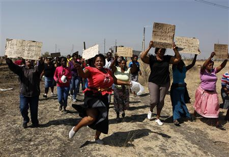 Women carry placards as they chant slogans, as they protest against the killing of miners by the South African police on Thursday, outside a South African mine in Rustenburg, 100 km (62 miles) northwest of Johannesburg, August 17, 2012. REUTERS/Siphiwe Sibeko