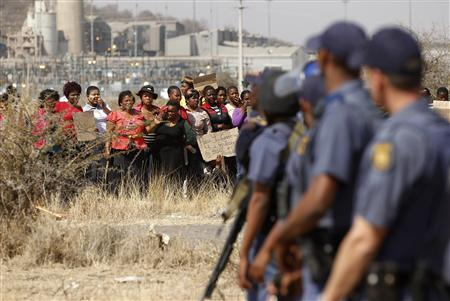Police look on as women carry placards in protest against the killing of miners by the South African police on Thursday, outside a South African mine in Rustenburg, 100 km (62 miles) northwest of Johannesburg, August 17, 2012. REUTERS/Siphiwe Sibeko