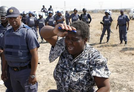 A local women cries as she confronts a police officer during a protest against the killing of miners by South African police on Thursday, outside a South African mine in Rustenburg, 100 km (62 miles) northwest of Johannesburg, August 17, 2012. REUTERS/Siphiwe Sibeko
