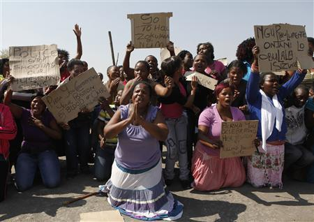 Women carry placards as they chant slogans to protest against the killing of miners by the South African police on Thursday, outside a South African mine in Rustenburg, 100 km (62 miles) northwest of Johannesburg, August 17, 2012. REUTERS/Siphiwe Sibeko
