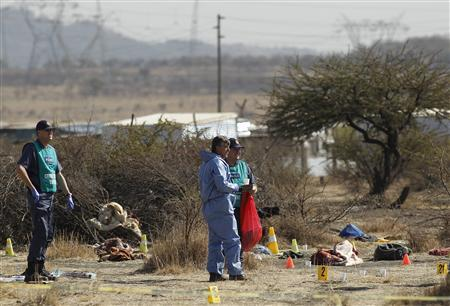 Investigators work at the crime scene where striking miners were shot on Thursday outside a South African mine in Rustenburg, 100 km (62 miles) northwest of Johannesburg, August 17, 2012. REUTERS/Siphiwe Sibeko