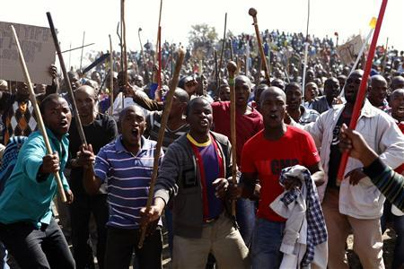 Protesters sing as they hold weapons outside a South African mine in Rustenburg, 100 km (62 miles) northwest of Johannesburg, August 16, 2012.REUTERS/Siphiwe Sibeko