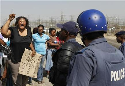 A local women gestures as she confronts a police officer during a protest against the killing of miners by South African police on Thursday, outside a South African mine in Rustenburg, 100 km (62 miles) northwest of Johannesburg, August 17, 2012. REUTERS/Siphiwe Sibeko