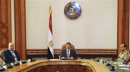 Egypt's President Mohamed Mursi (C) attends a meeting with Defence Minister General Abdel Fattah al-Sisi (R), Vice President Mahmoud Mekky and members of the Supreme Council of the Armed Forces at the presidential palace in Cairo August 16, 2012. Picture taken August 16, 2012. REUTERS/Egyptian Presidency/Handout