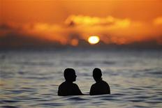 A couple watches the last rays of sunlight for 2011 at sunset from the waters off Waikiki Beach in Honolulu, Hawaii, December 31, 2011. REUTERS/Jason Reed