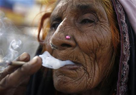 Sajadi, a ninety-year-old woman labourer, smokes a 'bidi' (an Indian leaf cigarette) at a roadside on the outskirts of New Delhi October 12, 2010. REUTERS/Parivartan Sharma