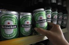 A woman reaches for a can of Heineken at a restaurant in Bangkok July 20,2012. REUTERS/Sukree Sukplang