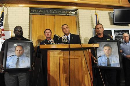 St. John the Baptist Parish Sheriff Mike Tregre (C), with Louisiana State Police Colonel Mike Edlmonson, (L), speaks at a press conference with two officers holding portraits of Brandon Nielsen (L) and Jeremy Triche, after an early morning shooting that left the two police officers dead and two other police officers injured in LaPlace, Louisiana August 16, 2012. The gunman fled the scene, and officers investigating the incident ended up at a trailer at a trailer court. While they interviewed two suspects, a person came out of the trailer with an assault weapon and fatally ''ambushed'' two officers. REUTERS/Cheryl Gerber