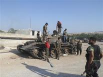 Members of the Free Syrian Army stand next to a captured Syrian Army tank in Bab Al Hawa on the outskirts of Idlib, near the Syrian-Turkey border August 14, 2012. REUTERS/Shaam News Network/Handout