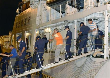 Chinese activists arrested on suspicion of violating the Immigration Control and Refugee Recognition Law at a disputed island in the East China Sea, known as Senkaku in Japan or Diaoyu in China, are escorted by Japan Coast Guard crew members as they disembark from a Japan Coast Guard patrol ship at a port in Naha on the southern Japanese island of Okinawa, in this photo taken by Kyodo August 16, 2012. REUTERS/Kyodo