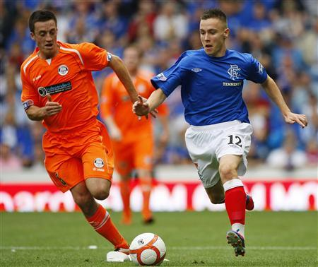 Rangers' Barrie McKay (R) runs with the ball as East Stirlingshire's Craig Hume challenges him, during their Scottish Football League division three soccer match at Ibrox stadium in Glasgow, Scotland August 18, 2012. REUTERS/David Moir