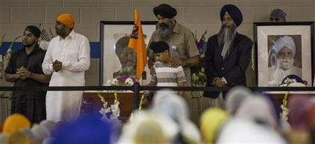 A young boy is comforted as he stands beside one the victims during the wake and visitation service for victims of last Sunday's attack at a Sikh temple, at Oak Creek High School, in Oak Creek, Wisconsin August 10, 2012. REUTERS/Tom Lynn