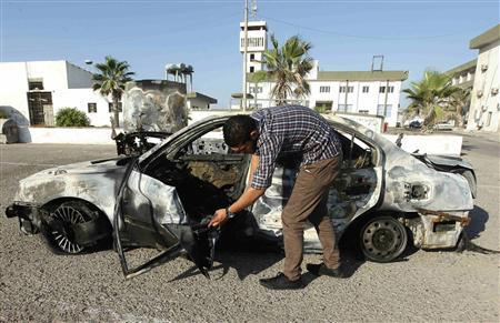 A military personnel examines a car, which exploded near a women's police academy, in Tripoli August 19, 2012. REUTERS/Ismail Zitouny