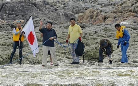 Unidentified members from a Japanese nationalist group and local assembly members are seen after landing on a Uotsuri island, part of the disputed islands in the East China Sea, known as the Senkaku isles in Japan, Diaoyu islands in China, in this photo by Kyodo August 19, 2012. REUTERS/Kyodo