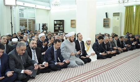 Syria's President Bashar al-Assad (3rd L) attends Eid Al Fitr prayers at al-Hamad mosque in Damascus August 19, 2012, in this handout photograph released by Syria's national news agency SANA. REUTERS/Sana/Handout