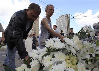 People lay flowers at the monument to the three victims of the 1991 coup to mark the 21st anniversary of the August Putsch in central Moscow, August 19, 2012. REUTERS/Sergei Karpukhin