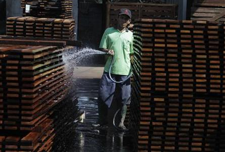 A worker sprays water onto piles of plank wood in timber company PT Larasati Multisentosa in Pasuruan, Indonesia's East Java province July 2, 2012. REUTERS/Sigit Pamungkas