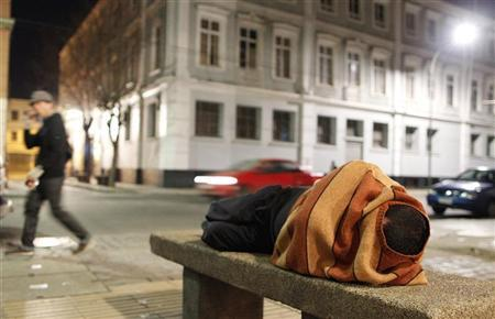 A homeless man sleeps on a cement bench in the downtown of Valparaiso, about 121 km (75 miles) northwest of Santiago, July 7, 2012. REUTERS/Eliseo Fernandez