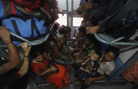 People from sit inside a train bound for the Assam state at the railway station in Kolkata August 18, 2012. REUTERS/Rupak De Chowdhuri