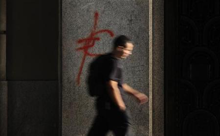 A man walks past a euro symbol painted in red on a branch of Santander bank in central Madrid, September 13, 2011. REUTERS/Susana vera