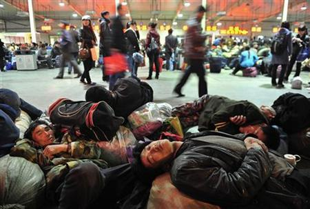 Migrants who come from rural areas to find jobs sleep as others travellers walk past at Shenyang railway station in Shenyang, Liaoning province, April 10, 2012. REUTERS/Stringer