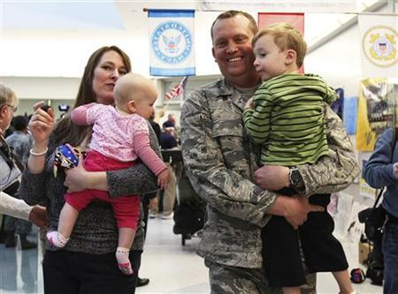 U.S. Air Force airman Lt. Col. Steven Vilpors walks with his wife Joanna and children Connor (R) and Alina (L) as he arrives in Baltimore Washington International Airport, Maryland December 20, 2011. REUTERS/Shannon Stapleton