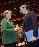 <p>Angela Merkel discutant avec Mario Draghi, le président de la BCE, sous les yeux de son prédécesseur Jean-Claude Trichet (au centre). Quand la chancelière allemande s'est résolue l'an dernier à soutenir la candidature de Mario Draghi à la présidence de la Banque centrale européenne, beaucoup y ont vu une forme de renoncement. Mais il semble aujourd'hui qu'elle ait plutôt trouvé un allié de poids dans cette opération. /Photo prise le 19 août 2011/REUTERS/Kai Pfaffenbach</p>