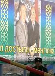 Казахский пограничник стоит на фоне плаката с изображением президента Казахстана Нурсултана Назарбаева (слева) и экс-президента Киргизии Аскара Акаева 28 марта 2005 года. Силовые структуры Киргизии ищут сбежавшего с оружием на автомашине пограничника, обвиняя его в расстреле в понедельник пяти человек на посту у границы с Казахстаном. REUTERS/Shamil Zhumatov