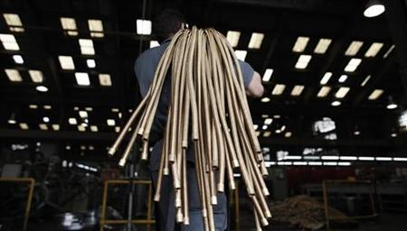 An employee carries copper hoses at the Sociedade Paulista de Tubos Flexiveis (SPTF) metallurgical company which manufactures flexible metal hoses, in Sao Paulo April 20, 2012. REUTERS/Nacho Doce