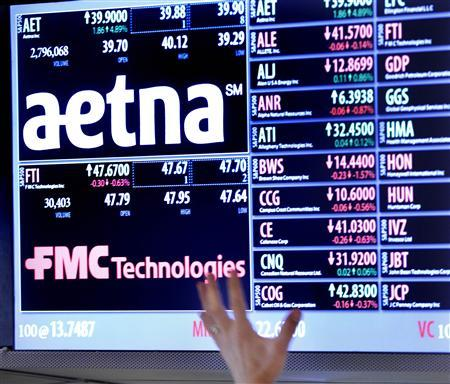 A trader points up at a display on the floor of the New York Stock Exchange August 20, 2012. Health insurer Aetna Inc said on Monday that it would buy rival Coventry Health Care Inc for $5.6 billion to increase its share of the fast-growing, U.S. government-backed Medicare and Medicaid programs. REUTERS/Brendan McDermid