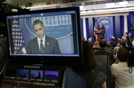 U.S. President Barack Obama is seen on a television monitor as he speaks in the press briefing room at the White House in Washington, August 20, 2012. REUTERS/Larry Downing