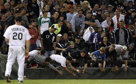 Fans reach for a foul ball during the MLB American League baseball game between Chicago White Sox and New York Yankees, in Chicago, August 20, 2012. REUTERS/Jeff Haynes