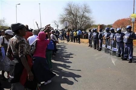 Police keep watch as women sing before the arrival of some of the 250 mine workers who were arrested last Thursday when they had a shoot out with police, at a Garankuwa court outside Pretoria August 20, 2012. REUTERS/Stringer