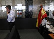 Трейдер разговаривает по телефону на фондовой бирже в Мадриде во время размещения испанских гособлигаций, 5 июля 2012 года. Доходность краткосрочных испанских долговых бумаг снизилась на аукционе во вторник, так как инвесторы ждут, что Европейский Центробанк выйдет на долговой рынок, но из-за неопределенности ставки остались довольно высокими. REUTERS/Andrea Coma