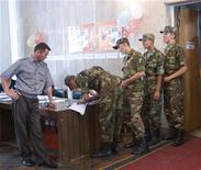 Киргизские военные получают бюллетени для голосования на избирательном участке в Бишкеке 23 июля 2009 года. Киргизские спецслужбы убили застрелившего пятерых пограничника, чье поведение власти увязали с дедовщиной, которая со времен СССР разлагает армии республик Центральной Азии, ставшей мишенью исламистов. REUTERS/Vladimir Pirogov
