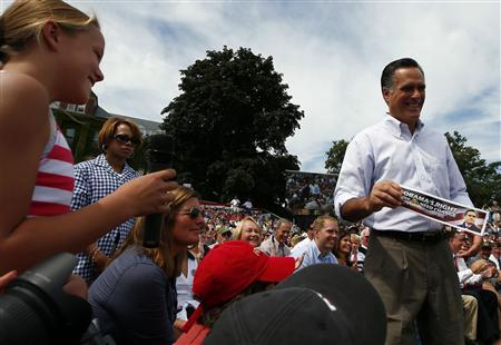 U.S. Republican presidential candidate and former Massachusetts Governor Mitt Romney accepts a bumper sticker reading: ''Obama's Right We Do Need Change'' from a young audience member at a town hall meeting campaign stop in Manchester, New Hampshire August 20, 2012. REUTERS/Brian Snyder