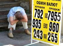 """Человек сидит на лестнице рядом с табло с курсами валют в Киеве 7 июня 2010 года. Нацбанк Украины, где через два месяца пройдут парламентские выборы, говорит, что может продолжить смягчение монетарной политики для поддержки замедляющегося роста экономики и ждет """"прогнозируемой"""" динамики курса гривны, несмотря на внешние шоки и пессимизм аналитиков. REUTERS/Gleb Garanich"""