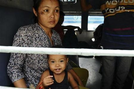 A woman from India's northeast waits with her child for the train to start as they make their way back home at a railway station in Bangalore August 17, 2012. India pressed social media websites including Facebook and Twitter on Tuesday to remove ''inflammatory'' content it said helped spread rumours that sparked an exodus of migrants from some Indian cities last week. REUTERS/Stringer