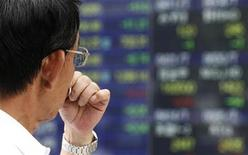 A man looks at an electronic board displaying share prices outside a brokerage in Tokyo July 25, 2012. REUTERS/Yuriko Nakao