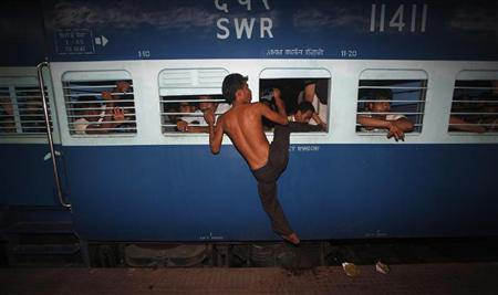 A man from India's northeastern state tries to board an overcrowded train through the window before it leaves for the Assam state at the railway station in Kolkata August 18, 2012. REUTERS/Rupak De Chowdhuri
