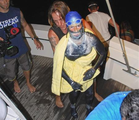 Veteran long-distance swimmer Diana Nyad is aided after she was pulled out of the water between Cuba and the Florida Keys early August 21, 2012. REUTERS/Christi Barli/The Florida keys News Bureau/Handout