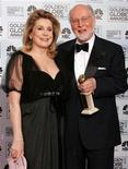 "Actress Catherine Deneuve (L) poses with composer John Williams after he won the Golden Globe for Best Original Score in a Motion Picture for ""Memoirs of a Geisha"" at the 63rd Annual Golden Globe Awards in Beverly Hills, California January 16, 2006."