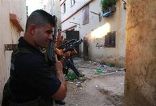 Sunni Muslim gunmen fire their weapons at the Sunni Muslim dominant neighbourhood of Bab al-Tebbaneh in Tripoli, northern Lebanon, during clashes with Alawites, August 21, 2012. REUTERS/Omar Ibrahim