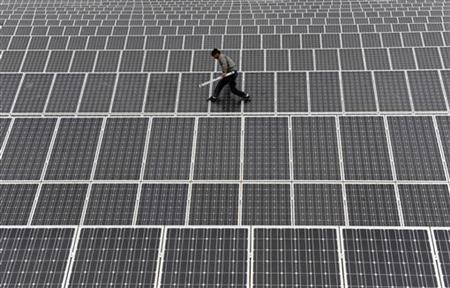 An employee walks on solar panels at a solar power plant in Aksu, Xinjiang Uyghur Autonomous Region May 18, 2012. REUTERS/Stringer