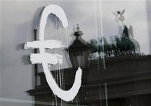 Символ евро на стеклянной двери Берлинской академии художеств, 3 июля 2012 года. Евро стабилен на азиатских торгах в среду после того, как достиг семинедельного максимума на предыдущей сессии, так как инвесторы ждут от регуляторов действий, направленных на разрешение долгового кризиса еврозоны. REUTERS/Thomas Peter