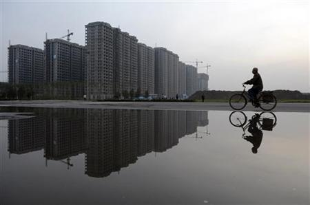 A man cycles past a residential complex under construction, which is reflected in a puddle, in Taiyuan, Shanxi province June 3, 2012. REUTERS/Stringer