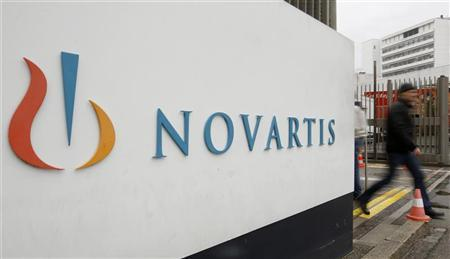 A man walks past the logo of Swiss drugmaker Novartis AG in front of a plant in Basel October 25, 2011. REUTERS/Arnd Wiegmann/Files