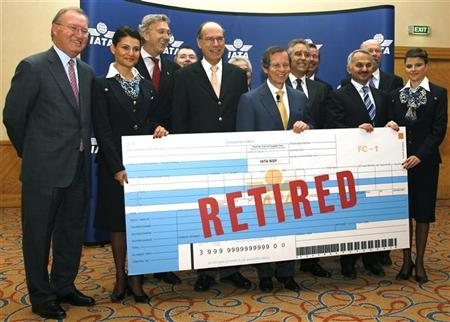 File photo of airline executives posing with a mock-up of the last paper ticket at an event in Istanbul May 31, 2008. REUTERS/Osman Orsal