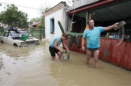 Local residents stand in a flooded courtyard of a house in the town of Krymsk, which has been seriously damaged by floods, in the Krasnodar region, southern Russia, July 8, 2012. REUTERS/Eduard Korniyenko